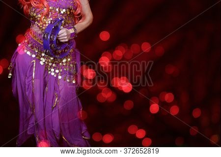 Belly Dancer Close-up With Tambourine And Red Bokeh