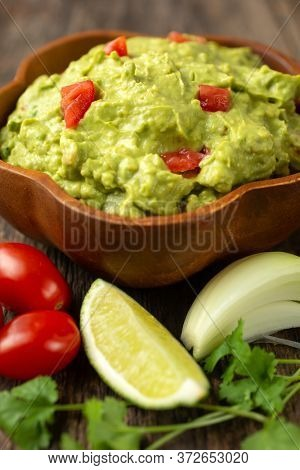 Close up of a bowl of traditional mexican guacamole  on a wooden background with fresh ingredient as tomato, onion, coriander and lime