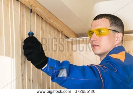 The Master In Blue Special Clothes Attaches The Wooden Structure To The Ceiling With A Screwdriver