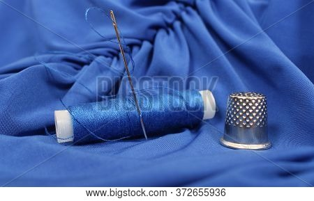 Blue Thread With Needle And Thimble On Blue Prom Dress