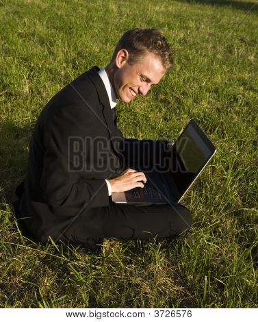 Happy Young Businessman Working In The Park