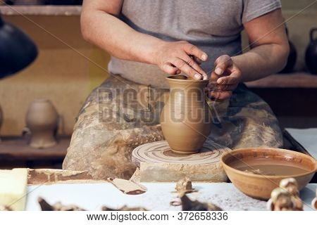 Potter At Work. Workshop Place. The Hands Of A Potter Creating Jar On The Circle.
