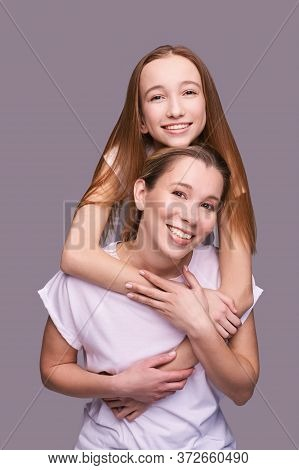 Elder Mother And Teenager Daughter Hug. Happy Family Portrait. Similar Smile. Next Generation Love.