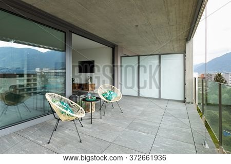 Large terrace of a luxury apartment. Two poltropne for relaxation and a small table are in the center.
