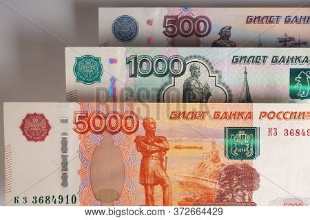 Russian Banknotes 5000, 1000, And 500 Rubles Hang In The Air Above The Gray Background. The Shadows