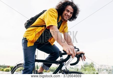 Happy Man Cycling On His Bike In The City Street. Cheerful Male Courier With Curly Hair In Yellow Sh