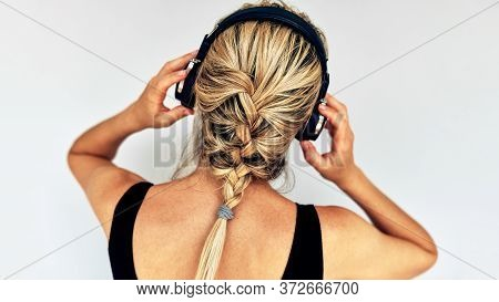 Rear View Image Of A Blonde Young Woman Listening To Music With Headphones. Caucasian Female Wearing