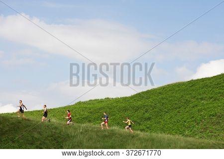 Group of people jogging up hillside