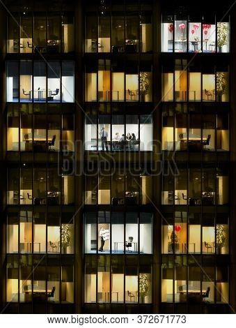 Cross section of office block with people working view from building exterior (full frame)