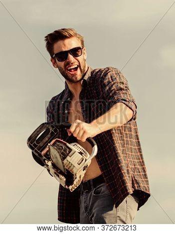 Handsome Man With Chainsaw Blue Sky Background. Gardener Lumberjack Equipment. Lumberjack With Chain