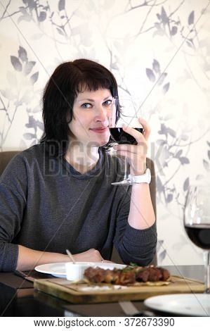 Girl Eats Steak With Wine. Girl Passionately Eats Steak. Steak And Wine.