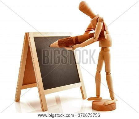 Concept With Desk, Board, Blackboard, Chalkboard, Frame And Wooden Toy Figure Writing With Pencil, P