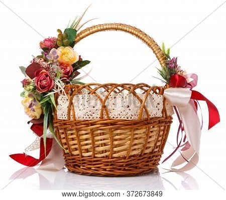 Easter Basket. Brown Wicker Basket With Colorful Floral Decor And Colored Ribbons On A White Backgro