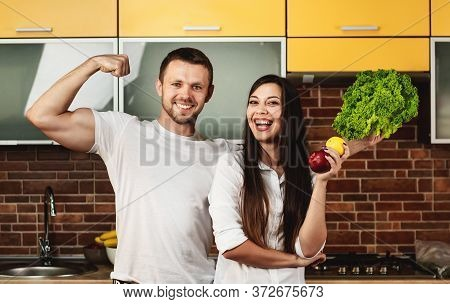 Happy Friends Preparing Food For Dinner, Posing In The Kitchen Holding Vegetables And Fruits. Man Sh