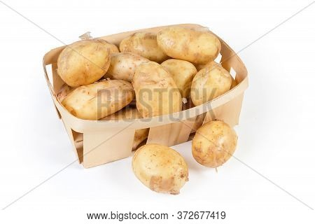 Raw Washed Yellow Young Potatoes With Unpeeled Thin Skin In The Small Wooden Basket And Beside On A