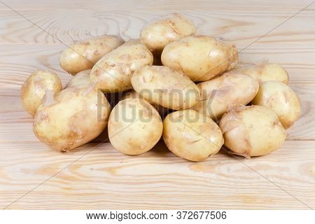 Pile Of The Raw Washed Yellow Young Potatoes With Unpeeled Thin Skin On The Rustic Table