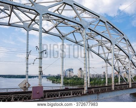 Fragment Of The Steel Riveted Arch Truss Of Railroad Bridge Against The City Buildings And Sky