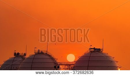 Industrial Gas Storage Tank On Orange Sunset Sky. Lng Or Liquefied Natural Gas Storage Tank. Spheric