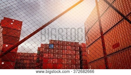 View From Fence Of Red Container Stacked. Container Logistics. Cargo And Shipping. Import And Export