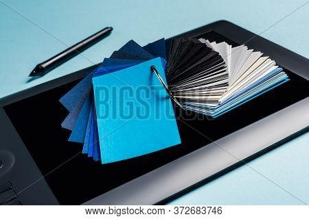 Close Up View Of Color Samples On Graphics Tablet And Stylus On Blue Background