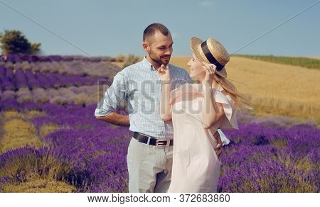 A Couple Is Standing In A Lavender Field. The Blonde In A Pink Dress And With A Straw Hat, Against T