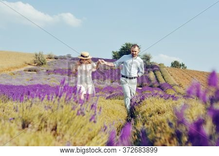 A Loving Couple Is Walking Along The Lavender Field, A Girl In A Dress And A Straw Hat With A Man Ho