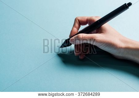 Cropped View Of Designer Holding Stylus Of Graphics Tablet On Blue Background