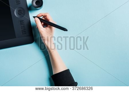 Top View Of Designer Holding Stylus Near Graphics Tablet On Blue Background