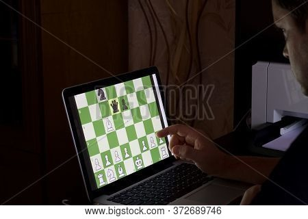 A Man Solves A Chess Problem Online. Chess Board With Figures On A Laptop Screen. Leisure In Self-is