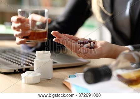 Close Up Of Entrepreneur Woman Hands Attempting Suicide With Pills And Alcohol Sitting On A Desk At