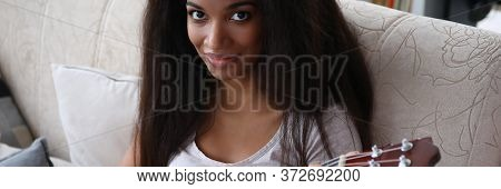 Dark-skinned Girl Sitting On Sofa Playing Ukulele. Beautiful Girl With Guitar In Her Hands. Song Wit