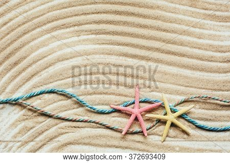 Two Colored Starfish And Two Colored Marine Ropes On Textured Wavy Sand. Top View.