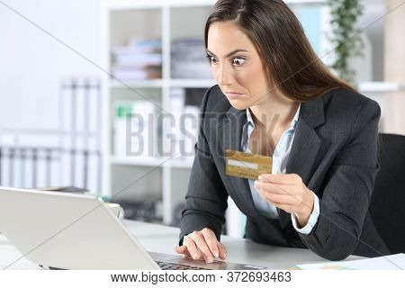 Perplexed Executive Woman Pays Online On Laptop With Credit Card Sitting On A Desk At The Office
