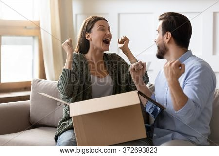 Excited Overjoyed Man And Woman Unpacking Awaited Parcel Together