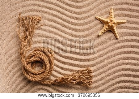 The Starfish Rope Lies On The Wavy Texture Sand. Top View. Place For Text.