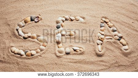 A Beach With An Inscription In English: Sea. The Letters Are Made By Sea Shells.