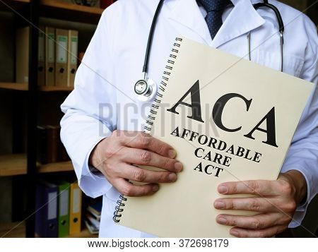 Doctor Holds A Book Affordable Care Act Aca.