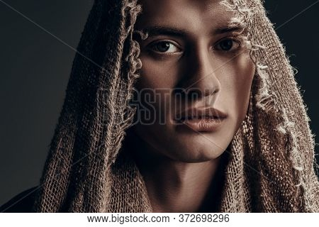 Portrait of a handsome young man in burlap clothes on a black background. Medieval wanderer, pilgrim.