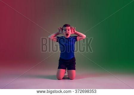 Winning, Goal, Screaming. Teen Male Football Player On Gradient Background In Neon Light. Caucasian