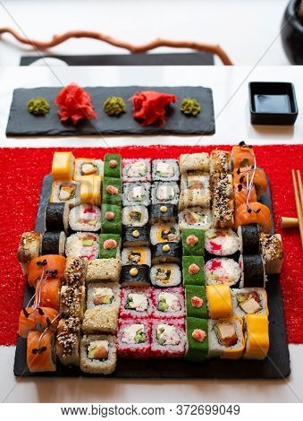 Different Types Of Rolls Stand On A Black Granite Board For Sushi On A Red Background.