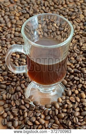 A Cup Of Coffee With Roasted Coffee Beans In The Background On A Kitchen Table