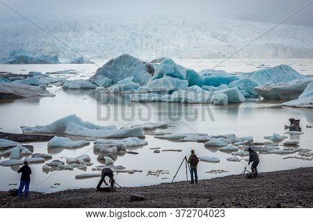 Fjallsarlon, Iceland - June 12, 2018: Tourists Takes Photos Of Icebergs Of Fjallsarlon Glacial Lagoo
