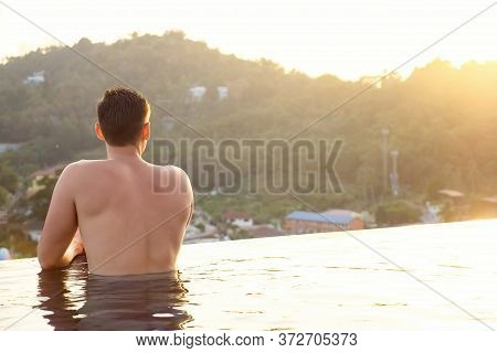 Man In Hotel Outdoor Swimming Pool Looking At Pictorial Tropical Forestry Hilly Landscape Backside V
