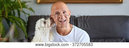 Handsome Man With Cute White Dog At Home