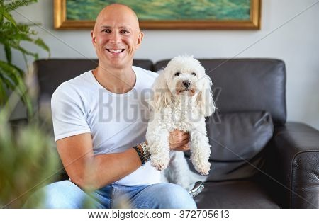 Handsome Man With Cute White Dog At Sofa