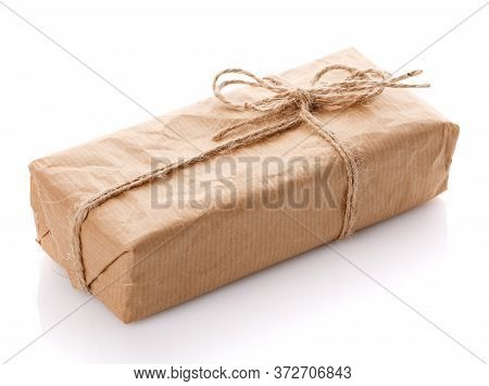 One Gift Box Wrapped With Kraft Paper And Burlap Ribbon On A White Background.