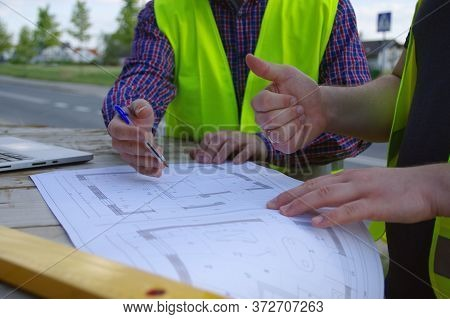 Engineer And Worker At A Construction Site. Teamwork. A Metaphor For Consensus, Success And Achievin