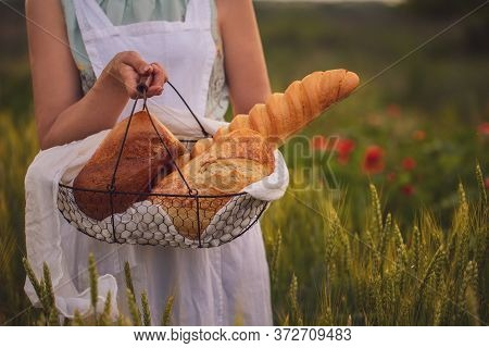 A woman carries bread in a field with wheat. Assorted bread in a basket in the hands of a woman. A w