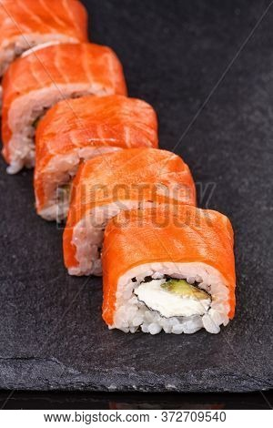 Philadelphia Sushi Rolls With Salmon And Cream Cheese And Avocado On A Black Slate Plate Close Up.