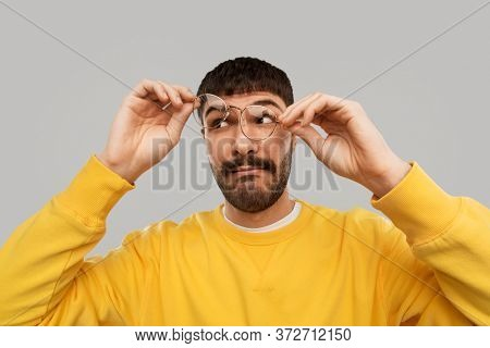 vision and people concept - goofy young man in glasses and yellow sweatshirt over grey background